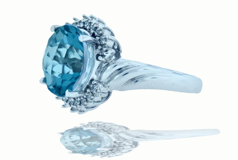 6.2 blue topaz cocktail ring with diamond halo. The center topaz of the ring measures 12.11 by 12.10 in a round cut. There are 18 - 1mm diamonds approximately .09 ctw that beautifully surrounding the center topaz. This fashion ring is set in 14k