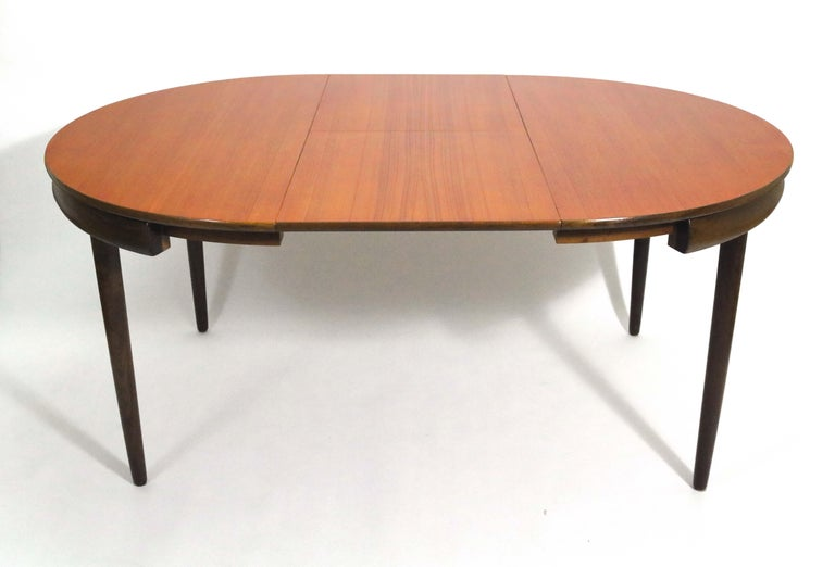 Hans Olsen's iconic teak dining table with 6 chairs by Hans Olsen for Frem Røjle.   The chairs tuck neatly into the outer rim of the table. These are the 4-legged chairs, not the 3-legged versions also creaated by Olsen for these tables.   The