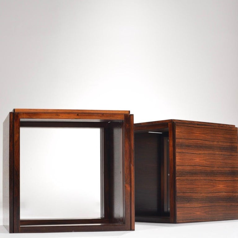 Rosewood square/cube nesting tables - each 'nesting table' contains three rosewood tables that fit into each other (creating a total of six tables when separated.) The squared legs and beautiful wood grain make these tables effortlessly sleek. Sold