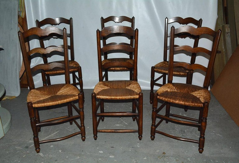 6 Country style ladder back dining chairs. Not a fully match set. One chair has straight horizontal back slats where as the others have a center v dip. Each with rattan seats. Measures: 36 inches x 16 inches x 13 inches. Seat height - 17