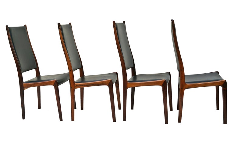 Set of 6 Johannes Andersen dining chairs in rosewood by Mogens Kold in Denmark. 4 side chairs and 2 armchairs. Armchairs measure 40 3/4