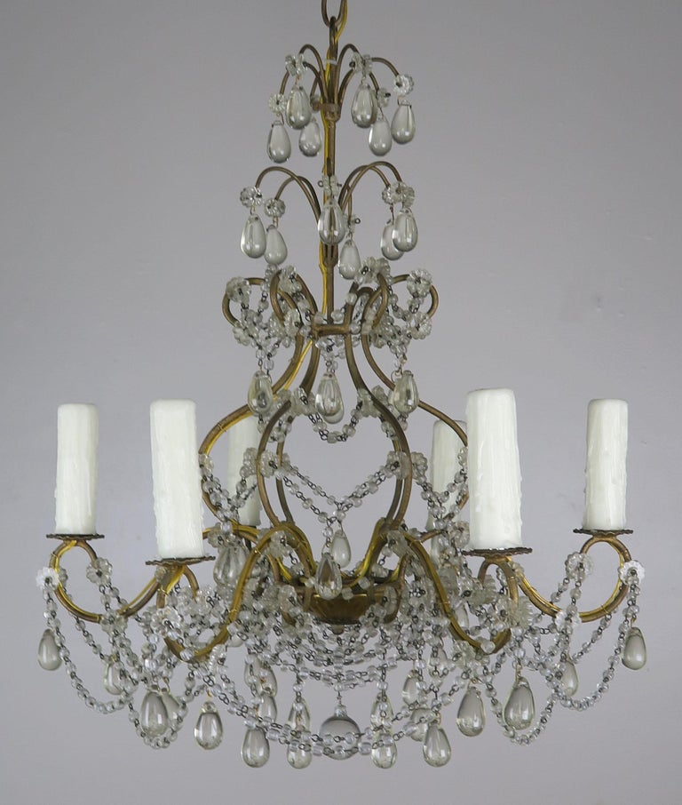 (6) light Italian gilt metal framed chandelier adorned with garlands of macaroni beads and tear shaped drops. The fixture is newly rewired with cream colored drip wax candle covers. Includes chain and canopy.