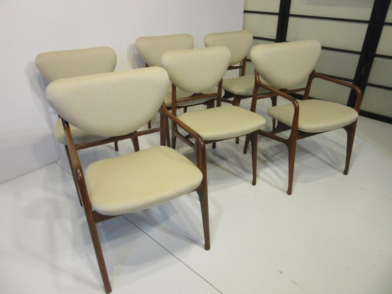 A set of six sculptural mahogany dining chairs with diamond quilted fabric in a creamy tone consisting of two armchairs and four side chairs. The bottom and back cushions have a floating affect making them appear light and airy on the well jointed