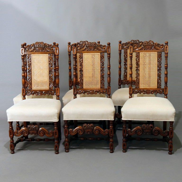 A vintage set of six Gothic style dining chairs by Kittinger feature heavily carved walnut frames with crown crests flanked by gadroon and foliate elements surmounting pressed cane backs with turned columns and upholstered seats raised on turned