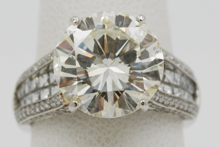 This diamond and platinum engagement ring showcases a 6.01ctw round brilliant cut diamond with M color and SI2 clarity. It also has two rows of blaze cut diamonds in the center row (.73ctw), pave diamonds in the gallery, outer rows and edges half