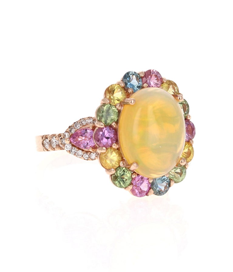 Simply a Beautiful Creation!   6.05 Carat Oval Cut Opal, Multi Sapphire and Diamond 14 Karat Rose Gold Cocktail Ring  Unique and beautifully designed cocktail ring that can be a great addition to anyone's accessory collection!     This ring has a