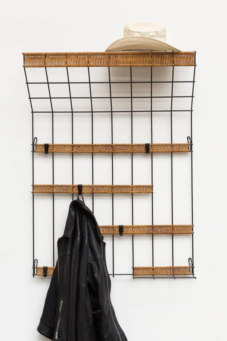 Black enameled metal wire grid wall mount coat rack with woven rattan detail and removable hooks. Very good original condition.