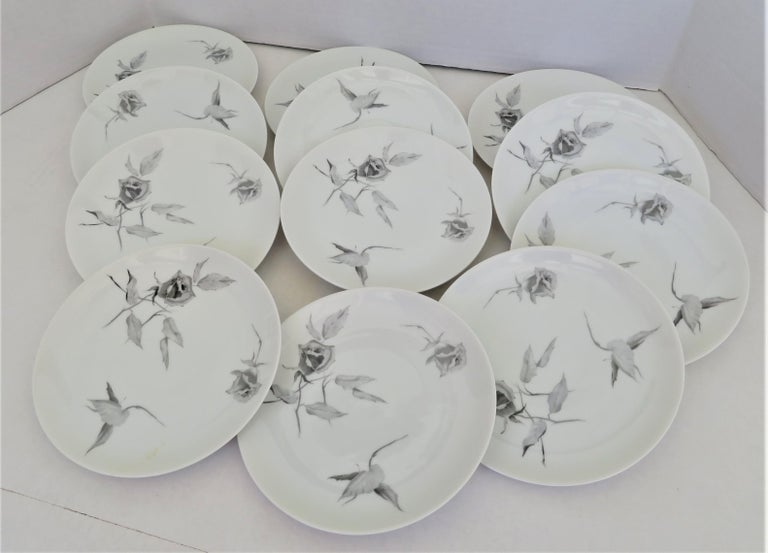 """A 1960s set of 12 Salad / Dessert plates (three sets available) in Raymond Loewy Jet Rose pattern and his iconic """"2000"""" form for Rosenthal from the 1960s. The decoration on the 7 3/4 inch plate is of Gray Roses that seem to be floating. This pattern"""