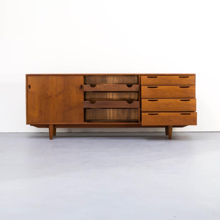 1960s teak sideboard by Ib Kofod-Larsen. This beautiful piece of furniture has an impressive teak wood corpus, that is framed with darker teak on the corpus' edges. All handles are elegantly worked out and give this sideboard its distinguished look.