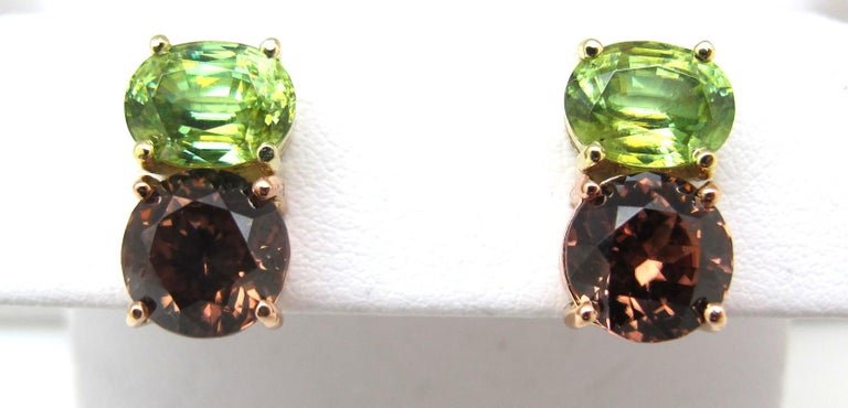 These color pairings are brilliantly bright! The two oval sphenes measuring 8.00 x 6.00 millimeters and weighing 3.44 carats total are paired with two rose zircon stones measuring 7.68 millimeters and weighing 6.11 carats in total elevate these