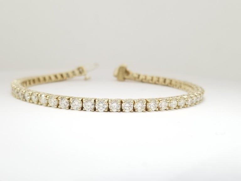 A quality tennis bracelet, round-brilliant cut diamonds. set on 14k yellow gold. each stone is set in a classic four-prong style for maximum light brilliance. 7 inch length. 3.2MM, Average Color H, Clarity VS.