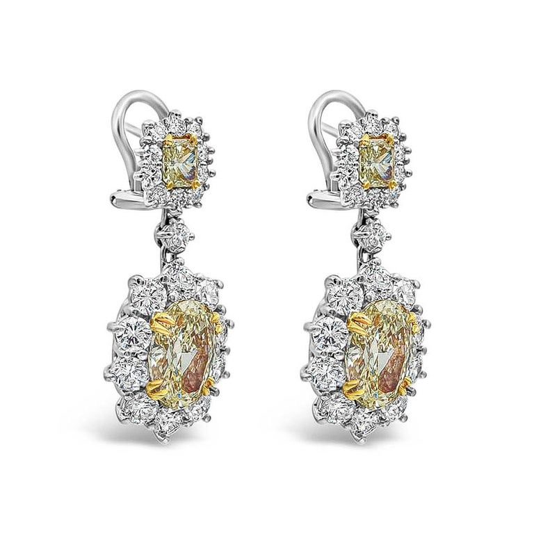 Burst out in style with this gorgeous pair of 18k white gold earrings. Showcases two fancy yellow oval cut diamonds weighing 6.15 carats surrounded by sparkling round diamonds in a creative floral motif. Suspended on vibrant radiant cut yellow