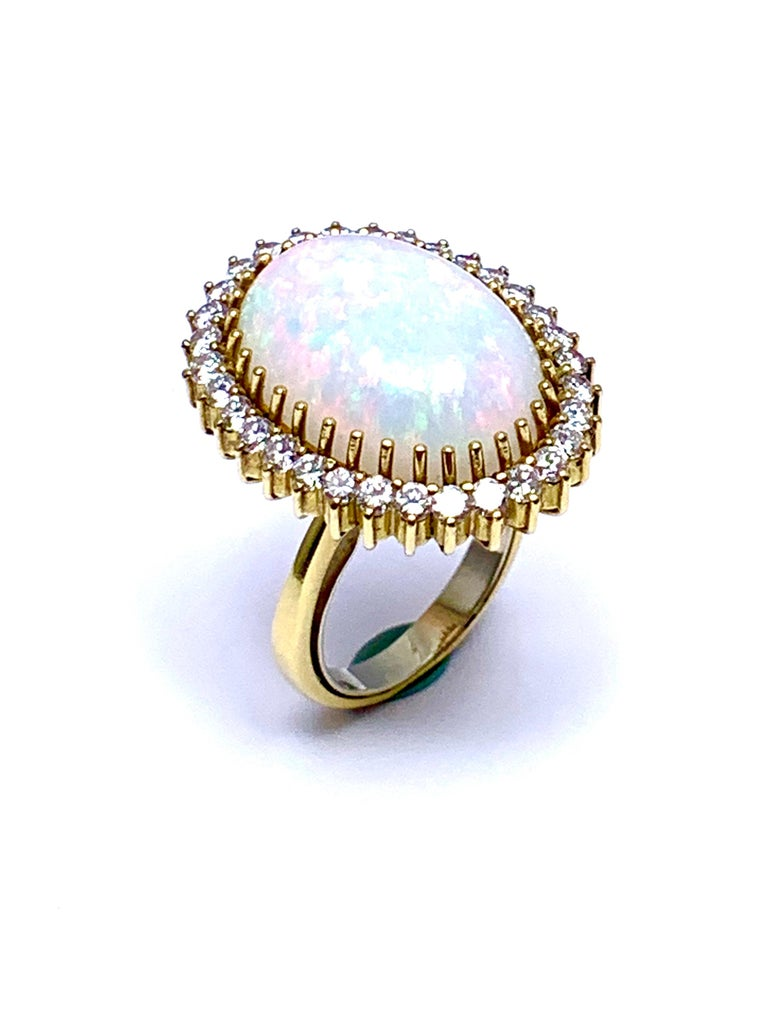 A beautiful oval cabochon White Opal and round brilliant Diamond cocktail ring.  The 6.16 carat Opal is prong set with a single row of diamonds surrounding,  The diamonds are graded as G color, VS clarity, combining for a total weight of 0.30