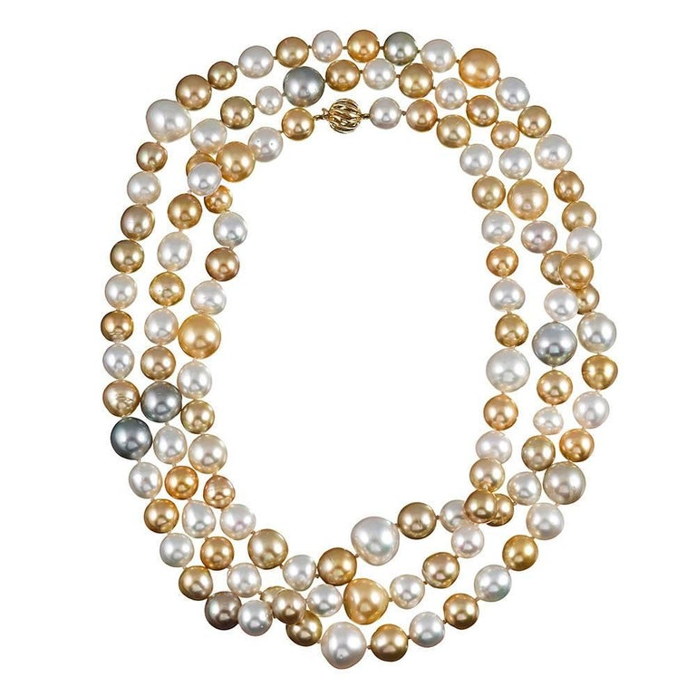 A gorgeous strand of 120 lustrous South Sea cultured pearls in hues of gold, white, silver, light grey and cream. The pearls range from 11.2 to 16.2 millimeters and are finished with a 14k yellow gold ball clasp.