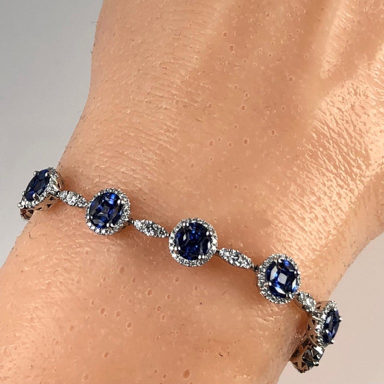 This gorgeous bracelet has eleven round sapphire clusters, each comprised of four marquise cut stones and a princess cut center. Each cluster is enclosed in a halo of round white diamonds. The halo clusters are linked by three round diamonds in