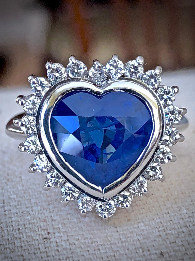 This treasure has a sapphire 5.35 carat, measuring  10.64 x 11.04  mm is TLG certified. The gem source is Burma. The royal blue color of this gorgeous center stone is complemented by 1.00 carat of round brilliant cut diamonds that encircle it in a
