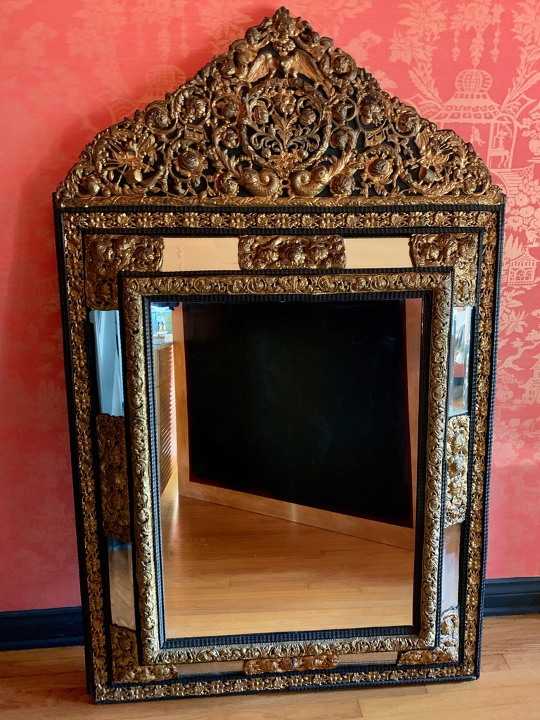 A monumental, stunning, and beautifully designed French Ebony repousse brass mirror with beveled glass. Hand-hammered with intricate French angels, drums. A very substantial and important look. The mirror is 75 pounds in weight. (A very small and