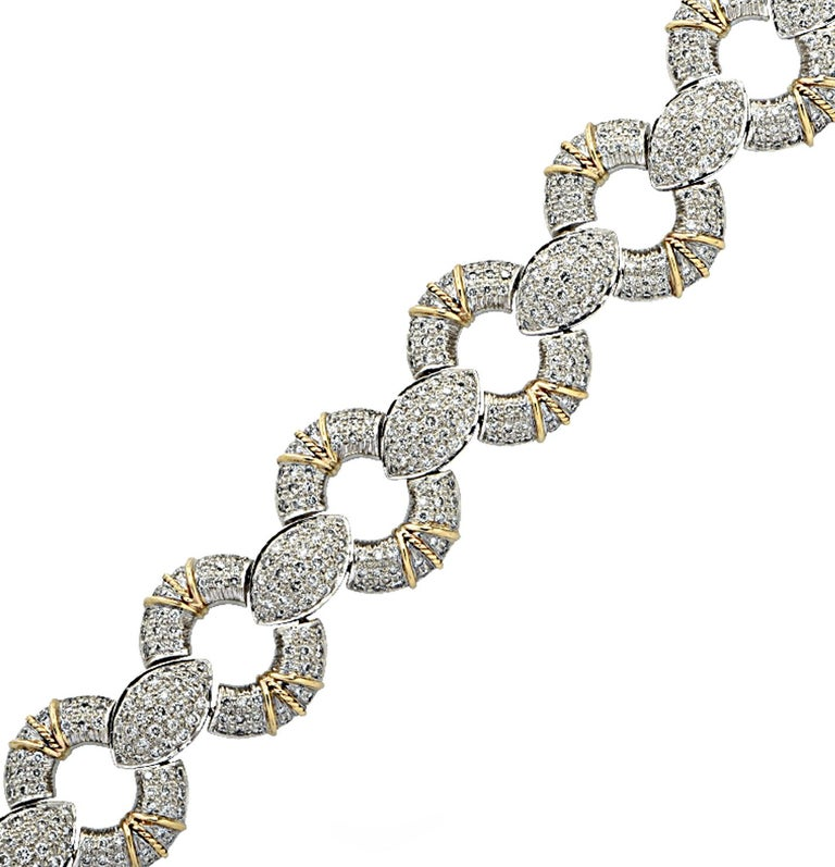 Gorgeous bracelet crafted in white and yellow gold featuring 650 round brilliant cut diamonds weighing approximately 6.5 carats total, G color, VS clarity. Open circle links, pave set with diamonds and adorned with yellow gold finishes, alternate