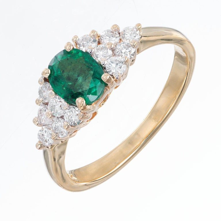 Emerald and diamond engagement ring. .65cts center oval emerald with triangle of 6 clustered diamonds on each side, in a 14k yellow gold setting.   1 oval emerald .65cts, 6.2 x 4.9mm approx. total weight .65cts 12 round diamonds approx. total weight