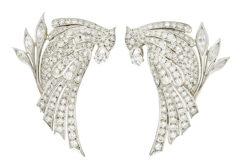 Clip style brooches designed as a pair of stylized quail birds clutching a round brilliant cut diamond in its beak weighing in total approximately 0.26 carat; G/H color with VS clarity  With sweeping geometric feather channels and olive branches