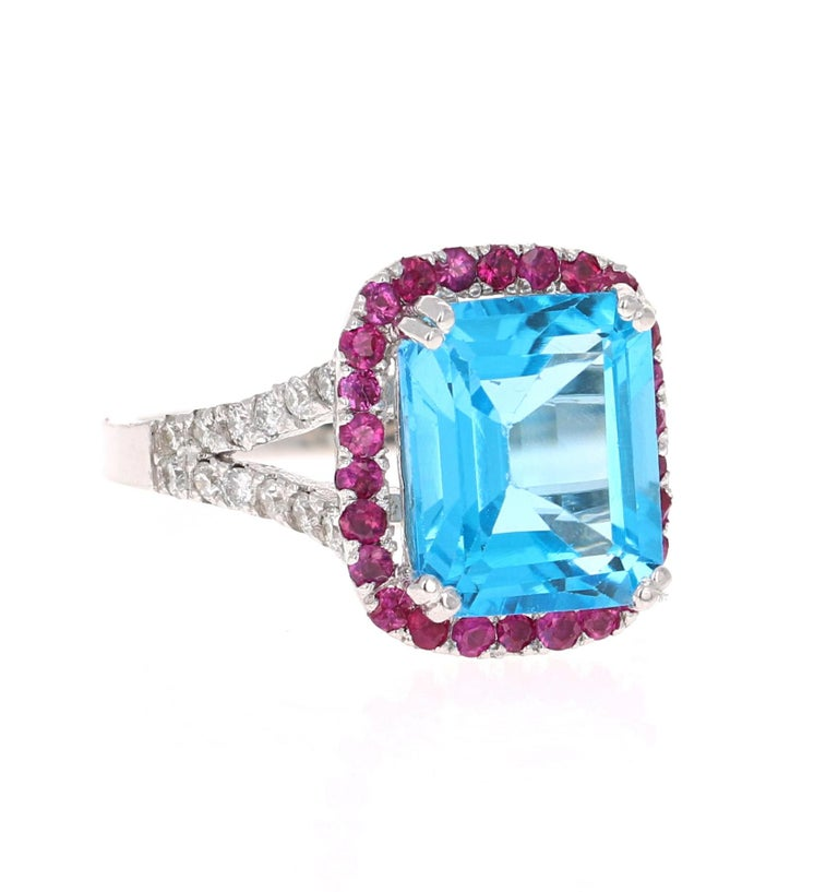 Beautiful and Unique to say the Least!   This Ring has a magnificent Emerald Cut Blue Topaz that weighs 5.62 carats and is surrounded by 26 Round Cut Pink Sapphires that weigh 0.52 carats and 24 Round Cut Diamonds along the shank that weigh 0.38
