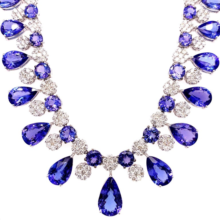 Majestic tanzanite diamond necklace earrings set. High lustre, transparent clean, violet-bluish, purple, pear, round faceted, 66.36 carats natural tanzanites mounted in an open basket with bead prongs, accented with a cluster of round brilliant cut