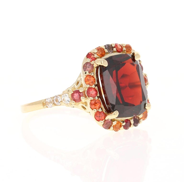 This ring has a Oval/Cushion Cut Garnet weighing 5.68 carats and is surrounded by multicolored sapphires weighing 0.98 carats. The total carat weight of the ring is 6.66 carats. The Garnet measures at 10 mm x 12 mm and the face of the ring measures