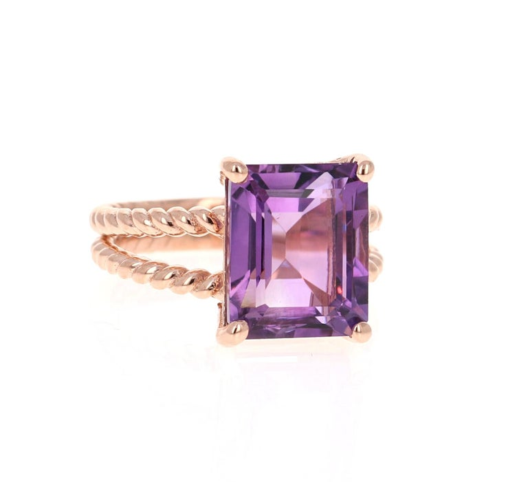 This Designer inspired Ring has a bright and vivid Emerald Cut Amethyst in the center that weighs 6.70 carats.  The setting is beautifully crafted in 14K Rose Gold and weighs approximately 5.0 grams. The ring is a size 7 and can be re-sized if