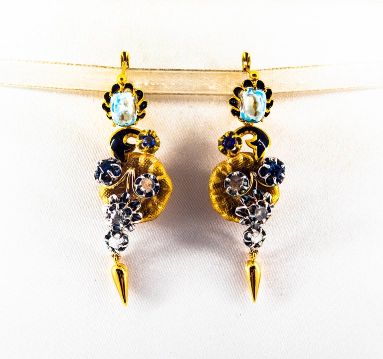 These Lever-Back Earrings are made of 9K Yellow Gold and Sterling Silver. These Earrings have 0.80 Carats of White Rose Cut Diamonds. These Earrings have 0.50 Carats of Blue Sapphires. These Earrings have 5.50 Carats of Blue Topaz. These Earrings