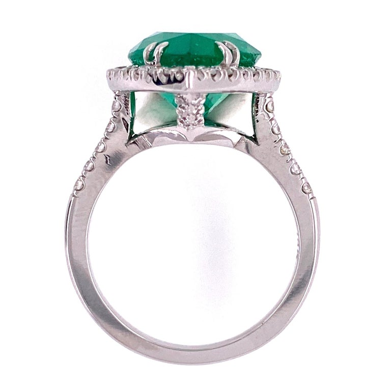 Beautiful and finely detailed pear shape Emerald and Diamond Cocktail Ring, center securely set with an Emerald weighing approx. 6.96 Carat surrounded by Diamonds weighing approx. 0.85 carats. Ring size 7, resizing available.  Hand crafted 18 Karat
