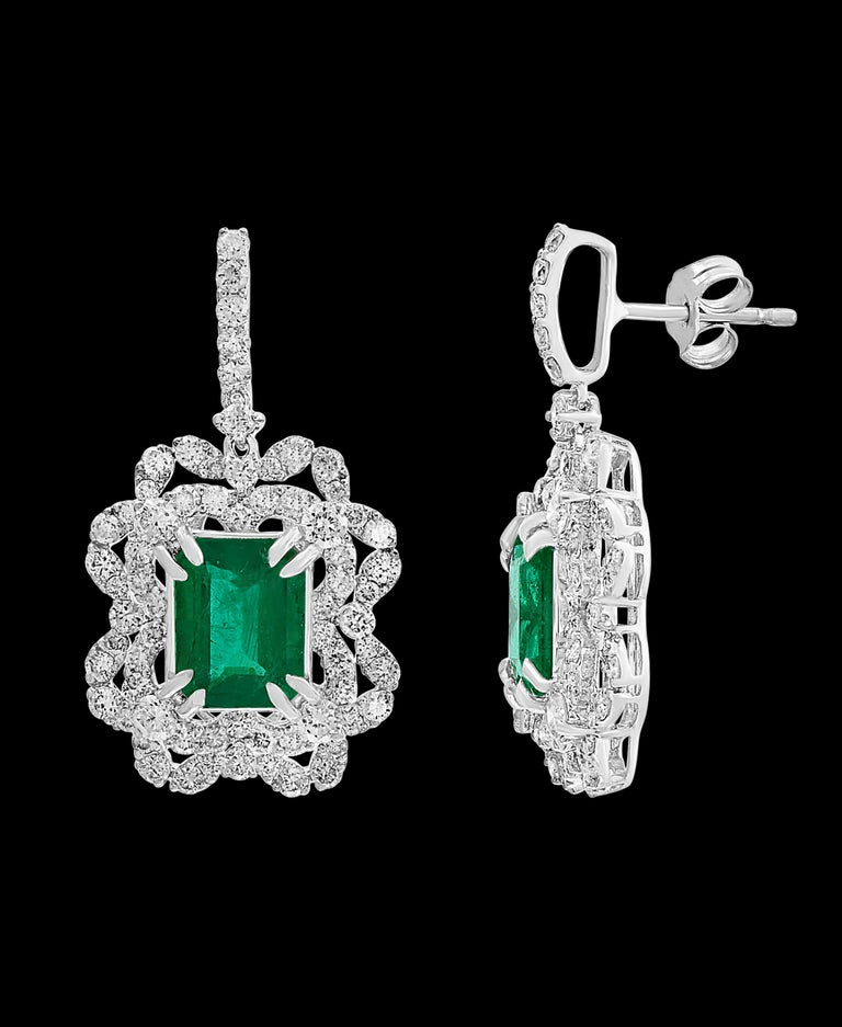 7 Carat  Colombian Emerald Cut Emerald Diamond  Hanging Earrings 18 K White Gold This exquisite pair of earrings are beautifully crafted with 18 karat White gold  weighing  9 grams Two fine Natural   Colombian Emerald  Cut Emeralds weighing