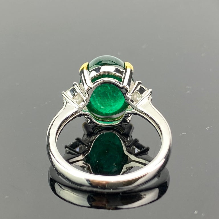 A beautiful three-stone engagement ring, with a 7.00 carat lustrous and transparent Zambian Emerald cabochon centre stone and 2 half-moon side stone diamonds; all set in 18K white gold. Currently a ring size US 6, but we can resize the ring for you