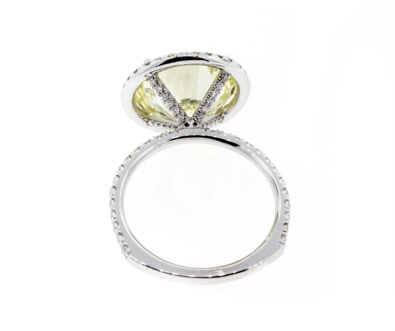 This incredible seven (yes, 7!) carat diamond engagement ring is perfection. Set in a platinum diamond halo setting with diamonds on the band and on the legs, this gorgeous fancy light yellow diamond engagement ring is the perfect way to propose to