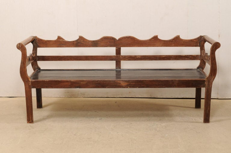A Brazilian peroba wood bench from the mid 20th century. This vintage wood bench from Brazil features a beautifully carved top rail, reminiscent of waves cresting, with a middle back slat board, horizontally placed at center. Sides are flanked