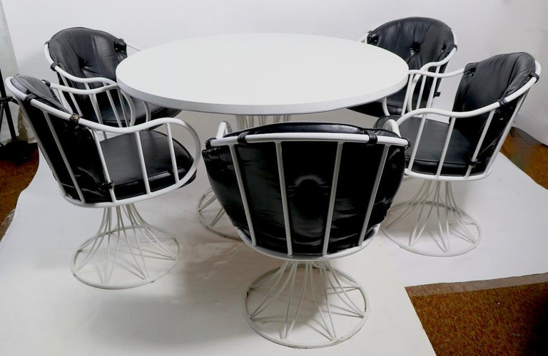 Fabulous and rare Richard McCarthy for Selrite dinette set consisting of 6 swivel armchairs, and 1 circular dining table the chairs have wrought iron frames in white paint finish with original tufted black vinyl backrests and seat cushions. The