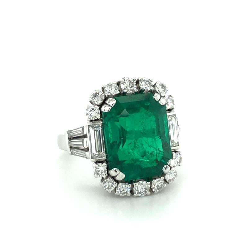 This elegant ring in 18 karat white gold features a stunning octagonal step-cut Colombian emerald of 7.03 carats. The entourage is prong set with 14 brilliant-cut diamonds of F/G colour and vs clarity, total weight approximately 0.60 carats. In