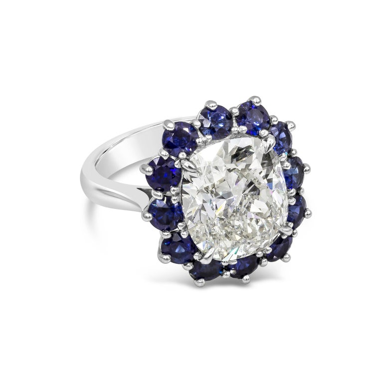 Showcasing a 7.04 carat GIA certified cushion cut diamond, surrounded by a single row of round cut blue sapphires. Sapphires weigh 2.60 carats total. Made in platinum. Certified by GIA as K SI1   Style available in different price ranges. Prices are