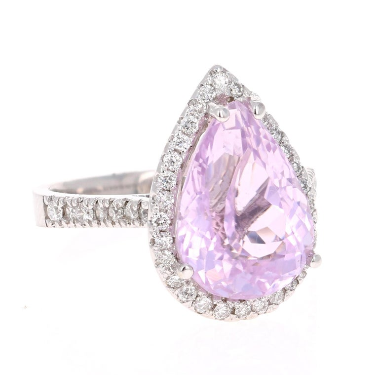 A lovely Engagement Ring Option or as an alternate to a Pink Diamond Ring! This simply stunning Kunzite Diamond Ring has a 6.54 Carat Pear Cut Kunzite as its center and has a beautiful simple halo of 44 Round Cut Diamonds that weigh 0.50 carats