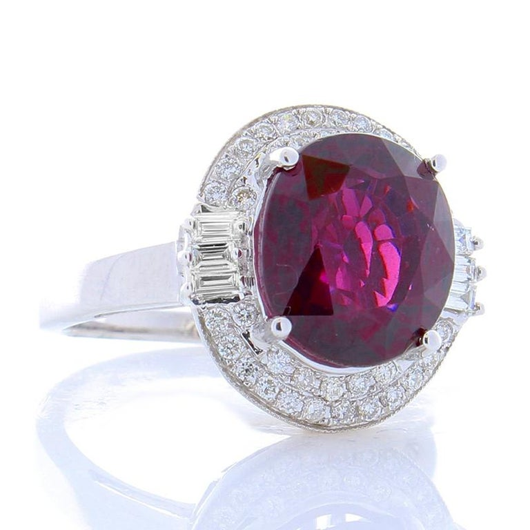 This striking piece features a flattering, fully faceted 7.05 carat -11.61 X 10.13 millimeter spessartite garnet that exhibits a vivid red hue. The gem source is Madagascar; its transparency and luster are superb. The gem is accompanied with a fancy