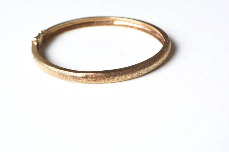 Textured stackable 1970s 14k gold bangle with latch style closure. Not marked, tested. Good overall condition. About 7
