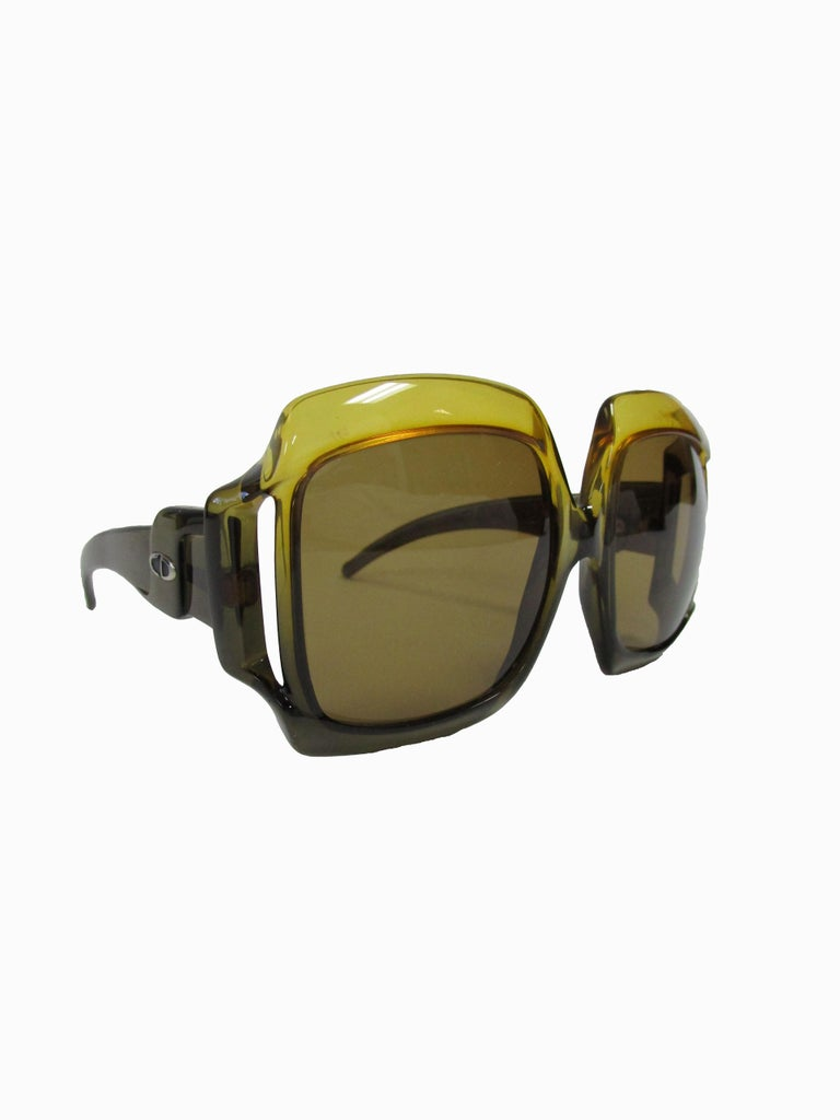 Beautifully crafted sunglasses by Christian Dior, they feature a sculptural optyl frame in green brown with tinted green lenses.  Christian Dior was the first designer brand to use optyl, before most sunglasses were made of acetate. Optyl is a
