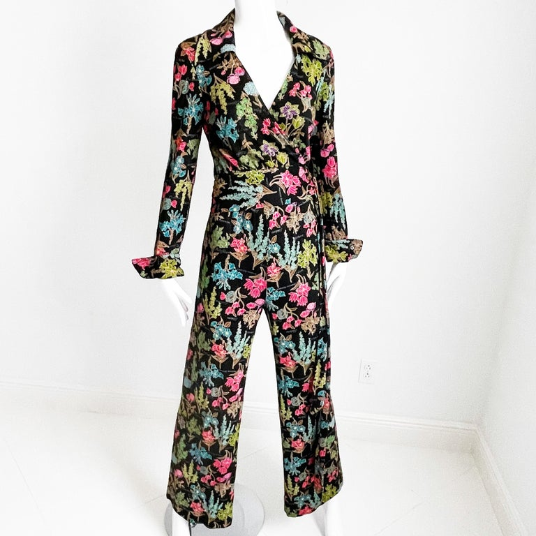 This ensemble was designed by Diane Von Furstenberg in the mid-1970s and includes her signature wrap style as a blouse with matching pants.  It's made from an acrylic jersey fabric, it features a colorful floral pattern against a black background.