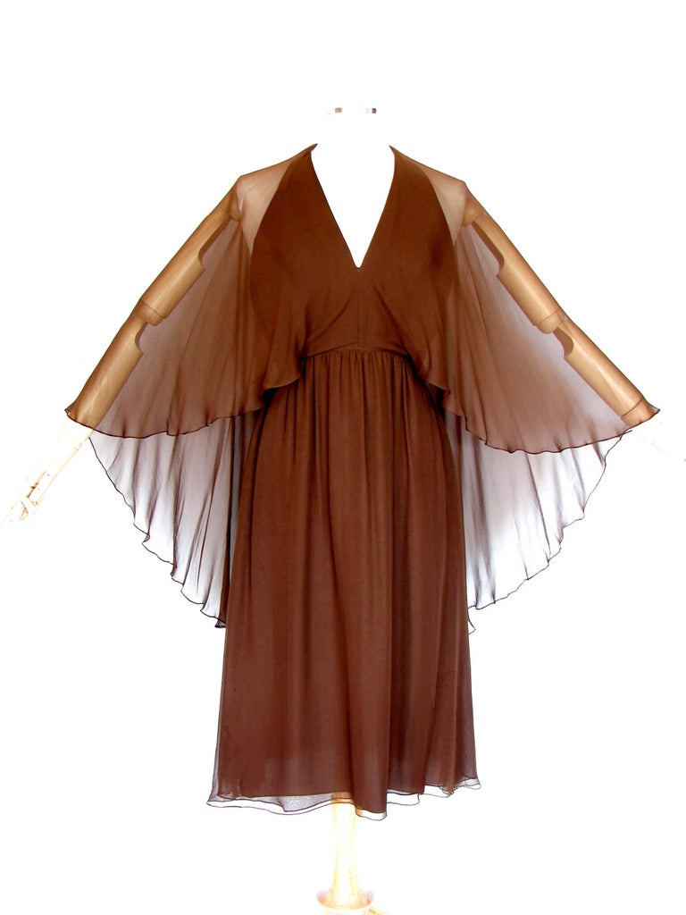 This Halston halter dress is from 1975 and has an ethereal quality with its attached sheer drapey shawl that can be worn as angel sleeves or pushed around the neck, shawl-style.  Fully-lined, it fastens in back with a zipper and several hidden snaps