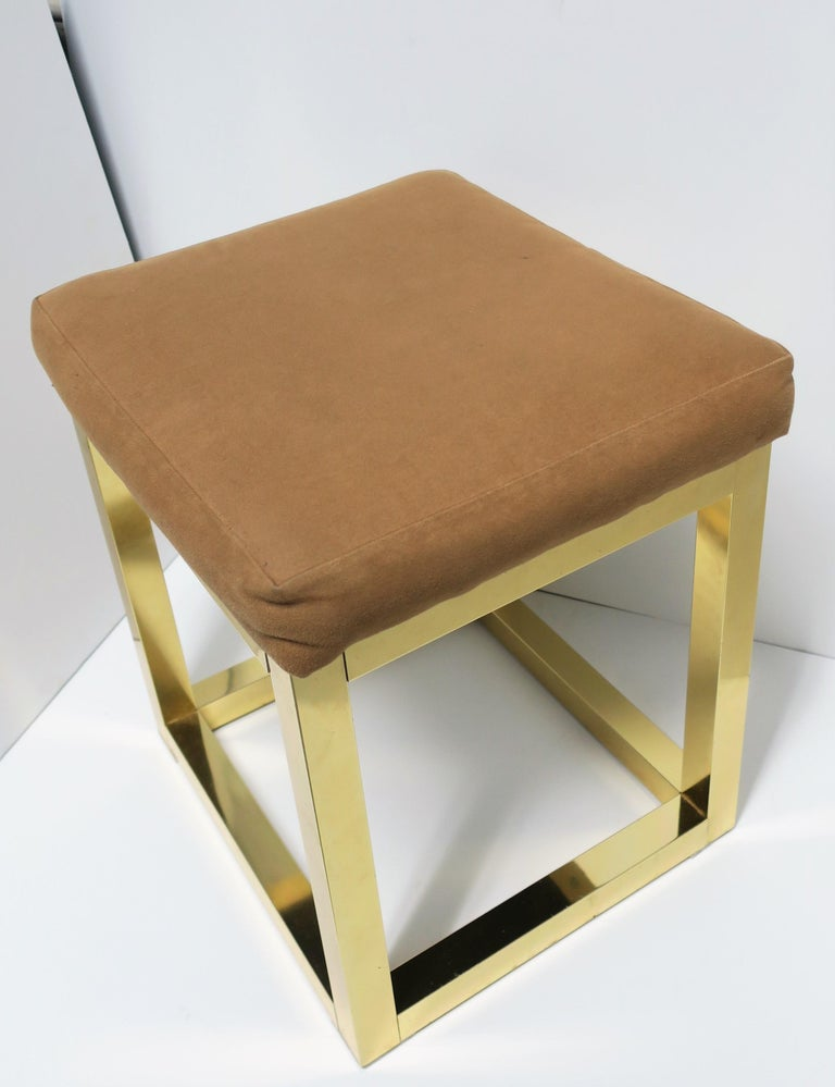 A 1970s modern brass bench or stool with upholstered seat cushion in the style of designer Paul Evans, circa 1970s.