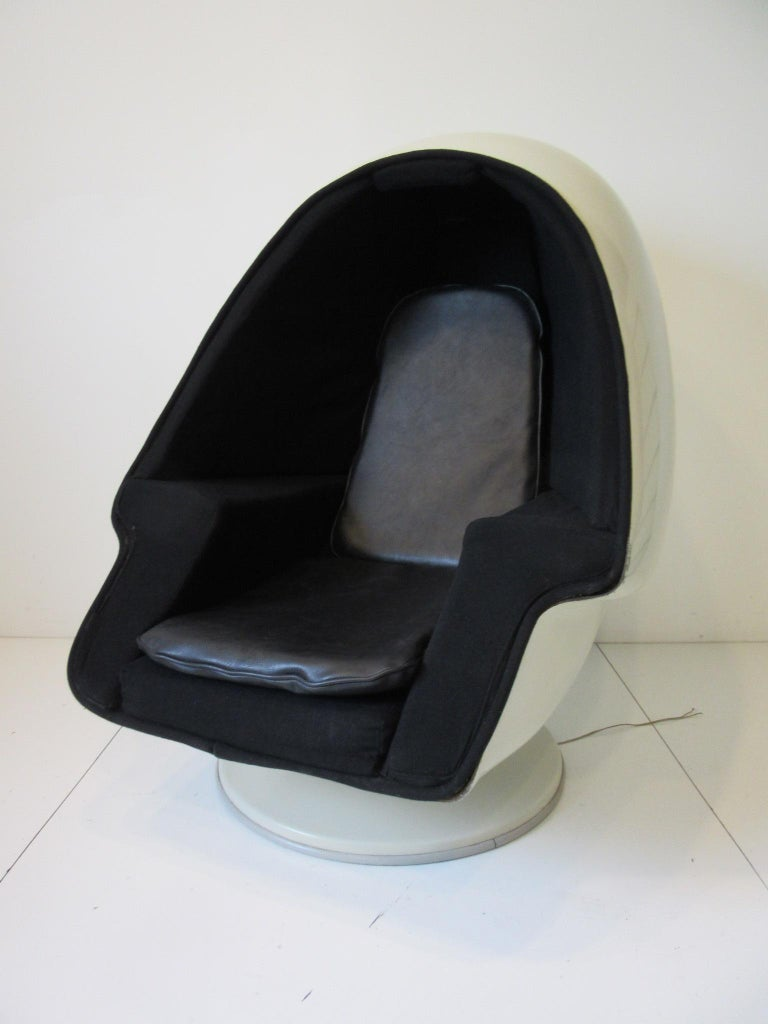A white fiberglass egg styled chair with matching ottoman having stereo speakers to each inside panel sitting on a round base. The interior is upholstered in the original woven black contract fabric thru out with arm rests and additional