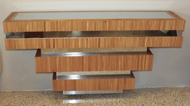 Successive layers of wood dowels and polished chrome make this 1970s wall-mounted console by Ernest Masi a very sophisticated blend of modern and organic.
