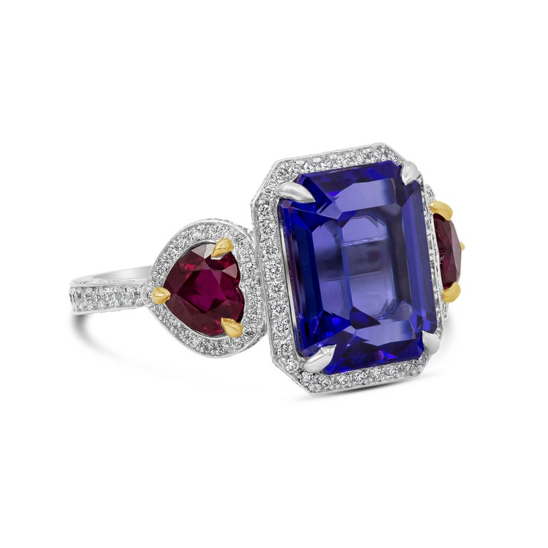 A brilliant design showcasing a purplish-blue emerald cut tanzanite, flanked by heart-shaped rubies on either side. Set in a diamond encrusted surmount made in platinum and accented with yellow gold. Rubies weigh 1.68 carats; diamonds weigh 1.21