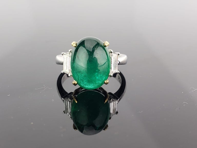 A beautiful three stone ring, with a 7.17 carat lustrous and transparent Zambian Emerald cabochon centre stone and 2 trapeze side stone diamonds; all set in 18K white gold. Currently a ring size US 6, but we can resize the ring for you without