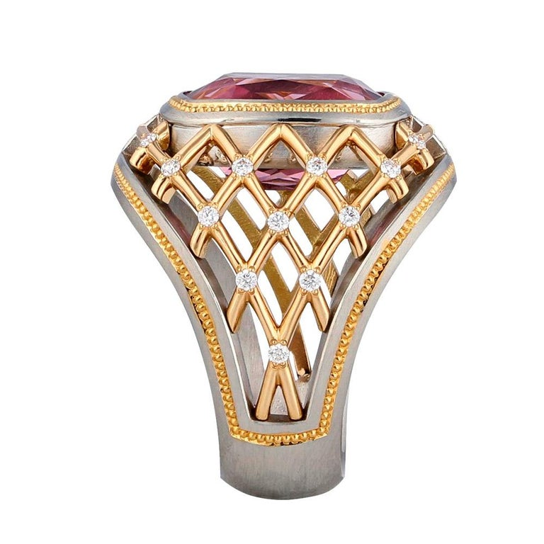 One of a kind 7.34 ct. Lotus Garnet set in Platinum with 22K Rose Gold hand engraved shaped inlay and Rose Gold grill. Accented with twenty-four .01 ct. round brilliant Diamonds. 20 mm across the top of the ring and 7mm wide at the bottom of the
