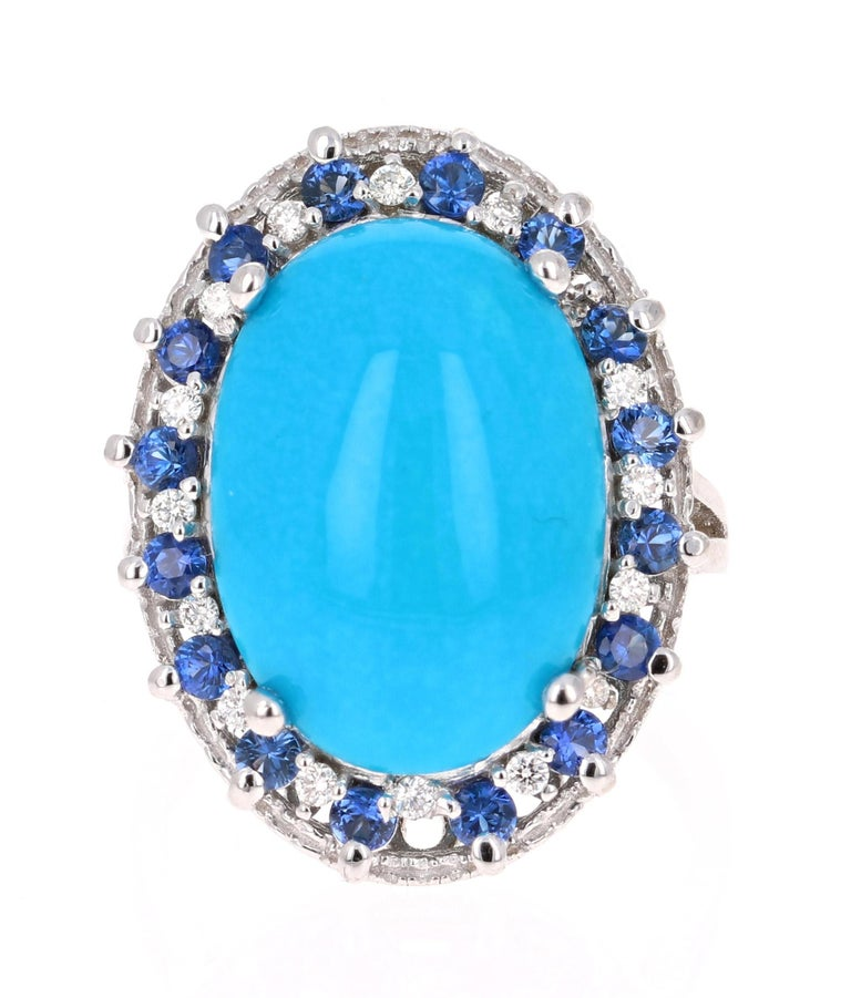 Beautiful Turquoise, Blue Sapphire and Diamond Cocktail Ring! This ring has an  Oval Cut Cabochon Turquoise that weighs 6.48 Carats and is artistically enhanced with Round Cut Diamonds and Blue Sapphires.  There are 16 Blue Sapphires weighing 0.79